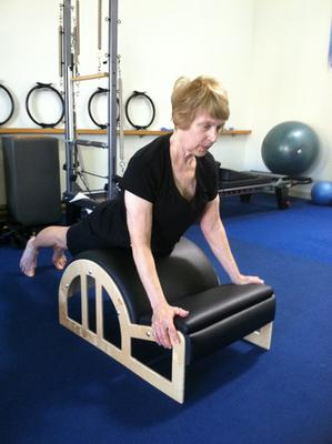 Exercise for winged scapula on the arc barrel.